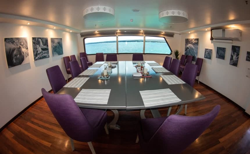 The dining room inside the Camila galapagos trimaran, purple chairs surround a grey table, a set of windows on one wall, and black and white painting are found on the others.