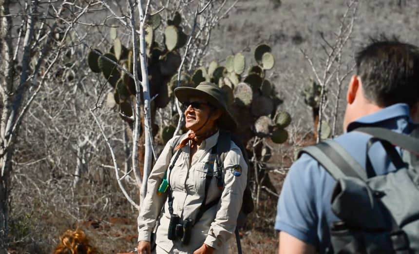 A female galapagos naturalist guide stands and speaks in front of a cruise group on rabida island, behind her are cactus and palo santos trees.