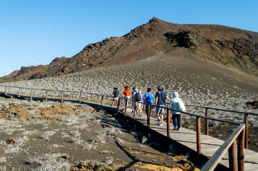 A shore excursion on a Camila Galpagos cruise a group of travelers walk on a wooden path up the desert like lava side of Bartolome Island to the top view point.