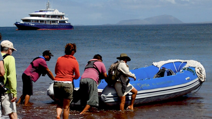 a group of travelers board an inflatable skiff or panga from the red sand beach on Rabida Island, in the distance the Camila galapagos ship floats in the ocean