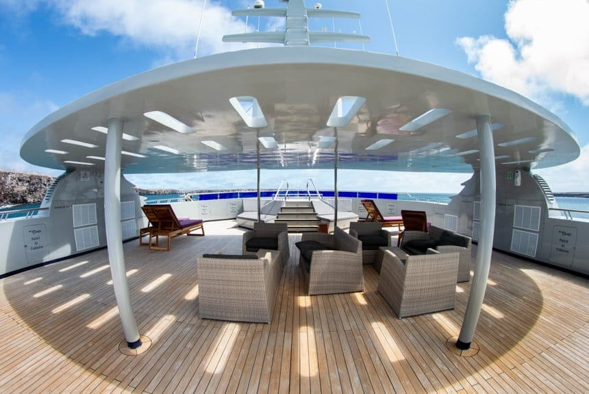 The sun deck aboard Camila Galapagos trimaran, a shade cover stands above a seating area in front of a jacuzzi with a panoramic view