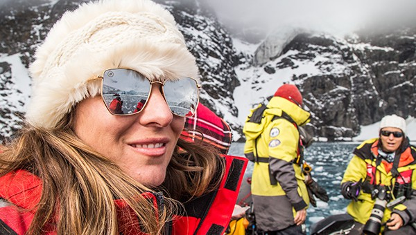 A female traveler in a fur hat, sunglasses and red jacket with sunglasses in Antarctica on a zodiac with other guests