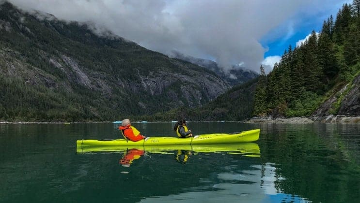 Tandem kayakers sit in calm waters under partly sunny skies in the Inside Passage on the North to True Alaska Adventure small ship cruise.
