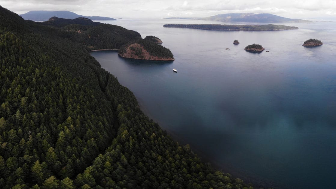 Aerial view of Cypress Island with green forest & emerald waters, with a small ship.