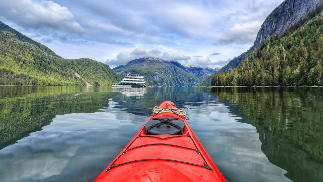 The front tip of a red kayak floats in the waters of Alaska, flanked by two forested mountainsides looking at small ship Alaskan Dream in the distance.