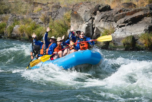 A group waves as they raft down the rapids of the Deschutes River in a large inflatable blue boat with yed-and-yellow paddles on a sunny day.