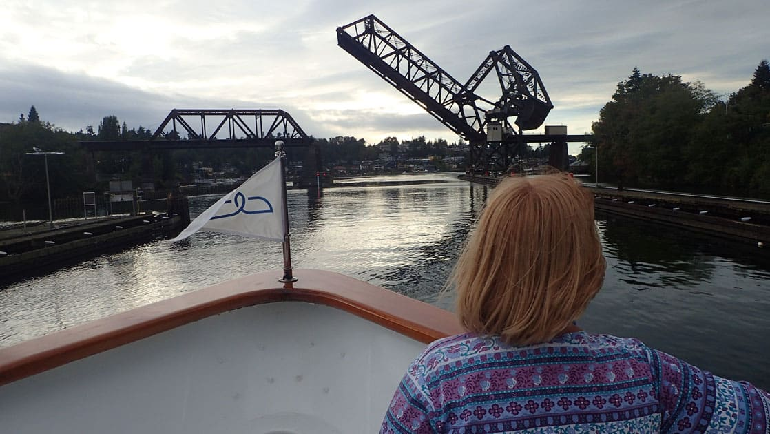 Red-headed woman stands at the front of a small ship out of Seattle as it approaches a drawbridge that's being raised.