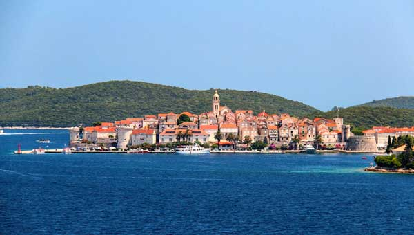 View of Dubrovnik Croatia with blue water and red rooftops with green hillsides