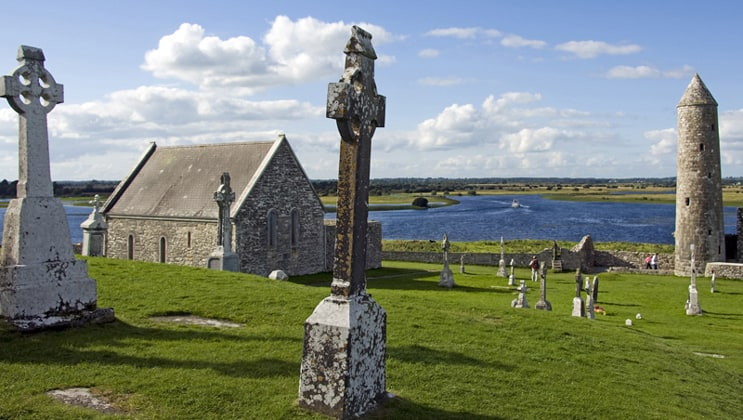 Small old stone church surrounded by green grass & stone crosses with calm river in the background on a sunny day during the Classic Ireland River Cruise.