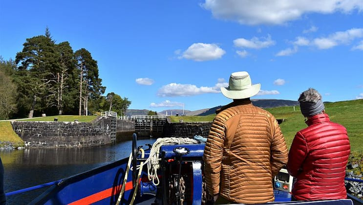 Man & woman in bright down jackets stand at the front of a hotel barge as it approaches a loch on a sunny day during the Classic Scotland Barge Cruise.