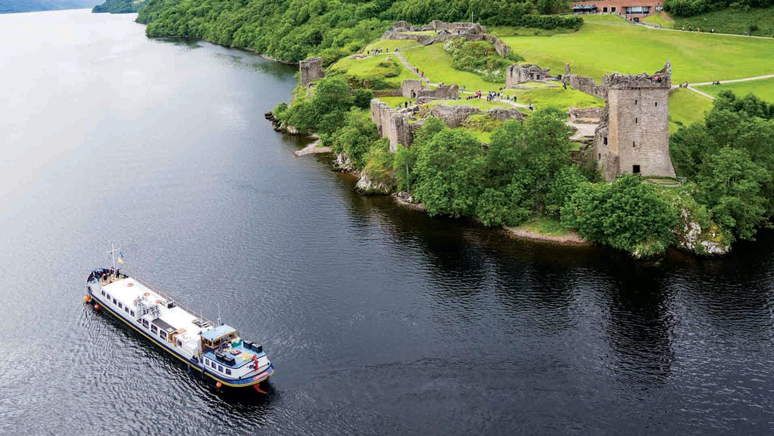 Aerial view of Urquhart Castle set along the Great Glen waterway, surrounded by bright green trees and grass with a hotel barge ship cruising by.