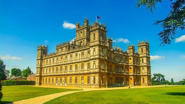 Highclere Castle with 3 stories, flags flying, green grass surrounding & blue sky, seen during a barge cruise in England.