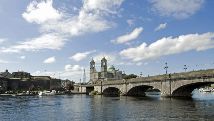 Calm, wide River Shannon running under the large stone bridge at Athlone under a sunny sky during an Ireland barge cruise.