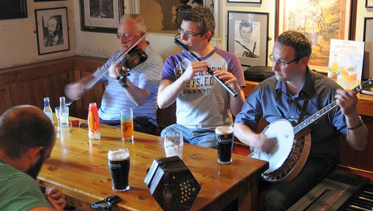 4 men play traditional Irish music in a pub during the Classic Ireland River Cruise.