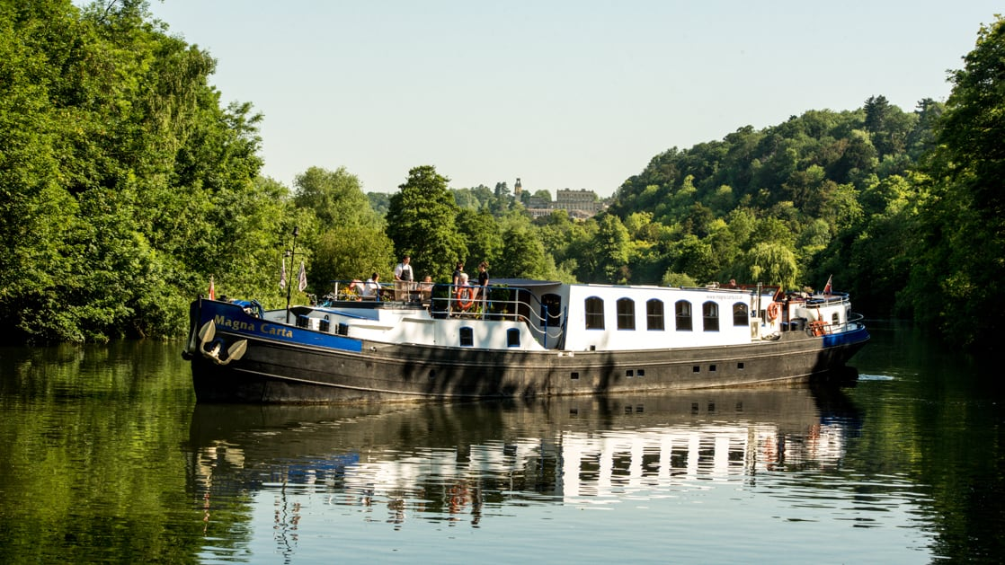 Black, white & blue-painted Magna Carta barge cruises the River Thames in calm waters with tree-lined riverbanks.