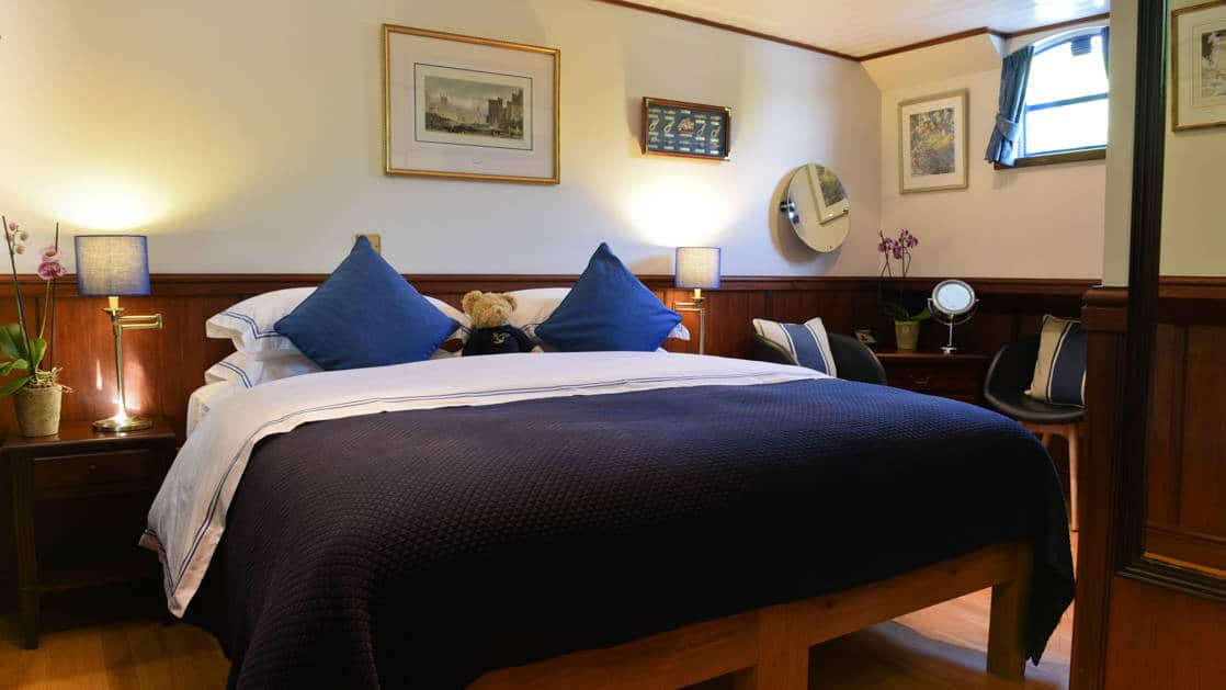 Suite with double bed, blue-&-white linens & pillows, small window, bedside tables & lamps, & wooden flooring & wainscoting aboard Magna Carta barge.