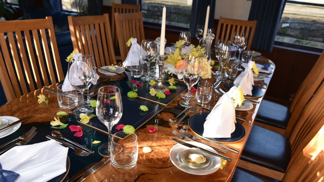10-guest dining table set for dinner with white linens, candles, flowers & wine glasses aboard River Thames barge Magna Carta.