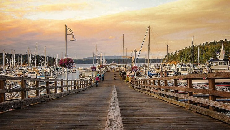 Long wooden wharf leading down to docks with small private boats in Friday Harbor, Washington, at sunset.