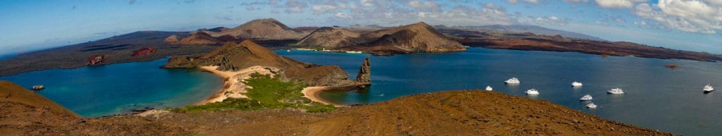 on a clear blue sky day a panoramic view from the top of Bartolome Island 7 small boats float in the water around the famous Pinnacle Rock