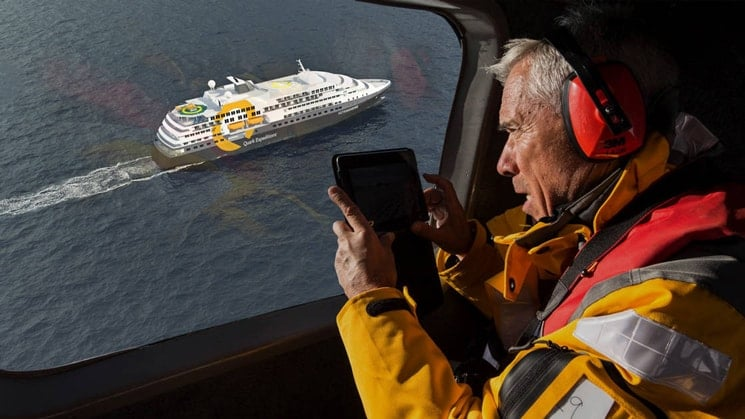 from a helicopter flying over head a man takes a photo of the new antarctic ship, the ultramarine.