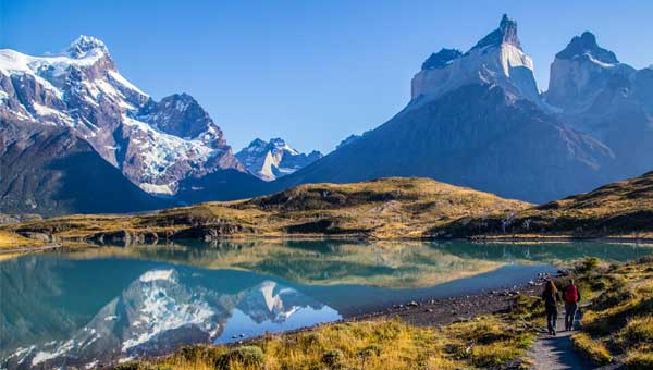 Two hikers walk on a lakeside trail in Patagonia with the mountains towering in front of them.
