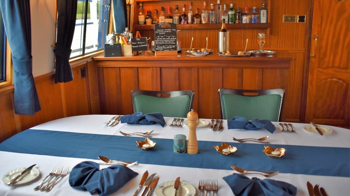 Dining room table set for a meal with white-&-blue linens & wooden bar behind aboard Scottish Highlander small riverboat.