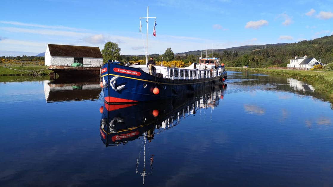 Scottish Highlander hotel barge sitting still in calm water with red-&-blue exterior & small white wooden building behind, on a sunny day in Scotland.