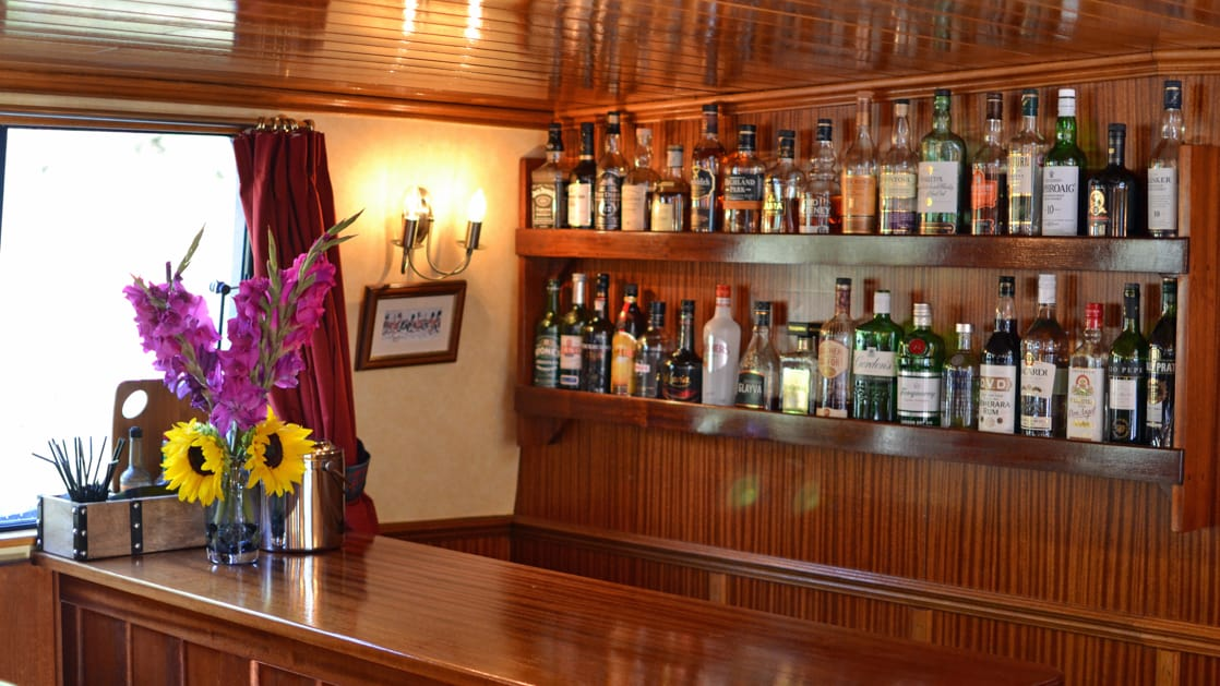 Warm wooden bar with 2 shelves of whisky behind & view window with vase of flowers beside it, aboard Scottish Highlander hotel barge.