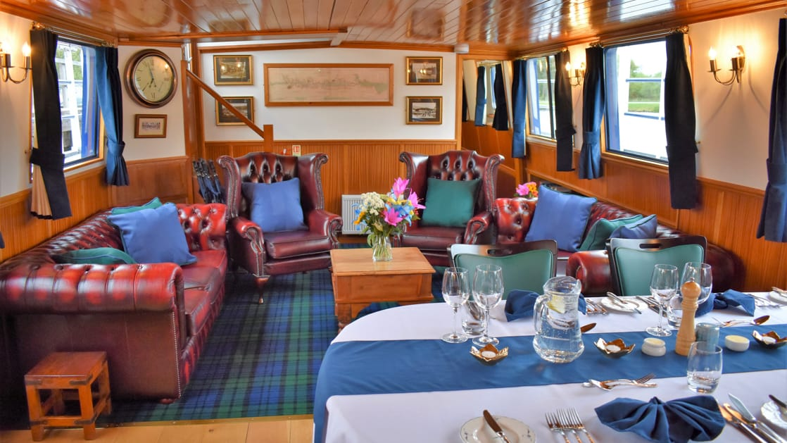Saloon indoor common area with dining table set for service & living room behind with leather armchairs & sofas aboard Scottish Highlander Caledonia Canal small ship.