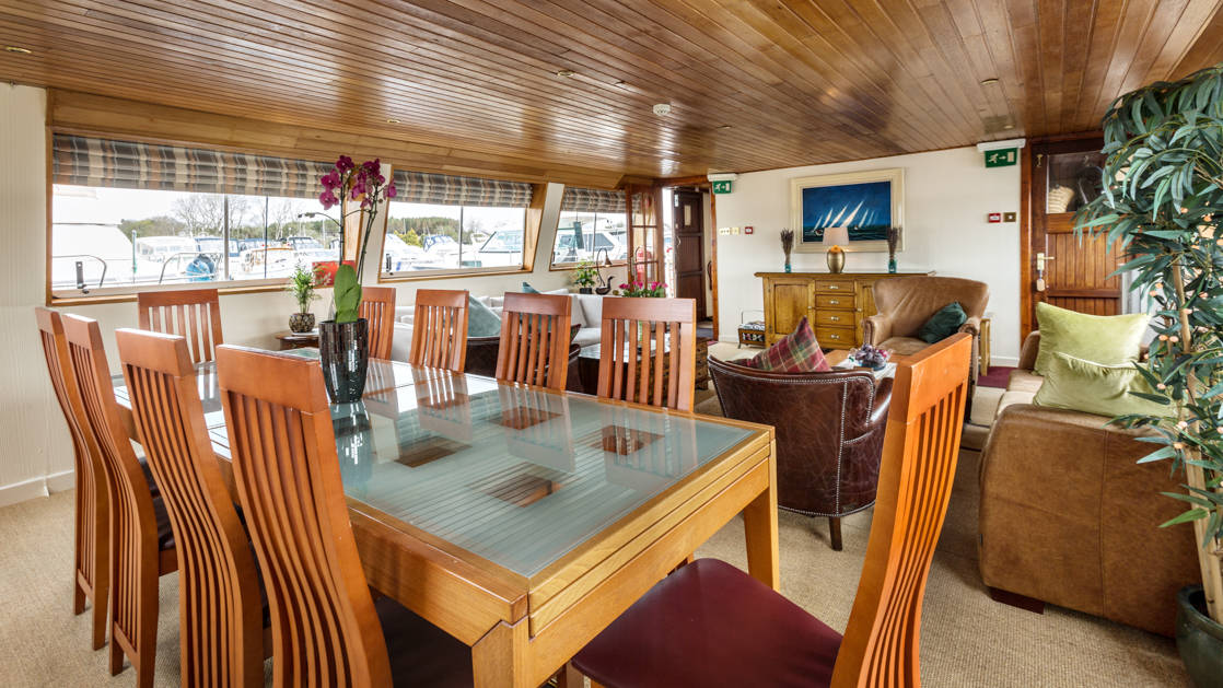 Dining table & saloon area with couches, chairs & coffee tables aboard Shannon Princess barge.