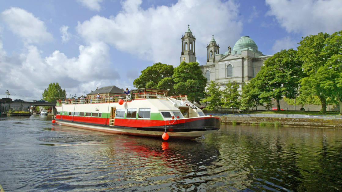 Shannon Princess barge cruising Ireland's River Shannon, past a castle & bright green trees on a sunny day.