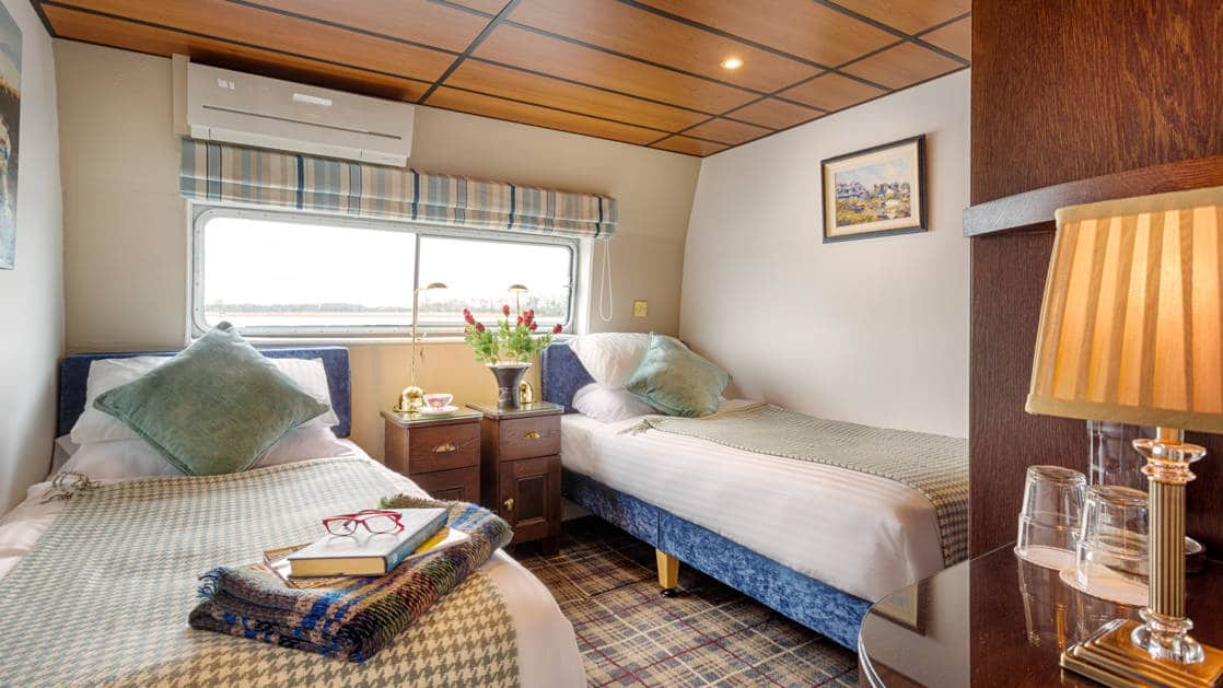 Suite aboard Shannon Princess barge with 2 twin beds, beige linens, large view window, bedside table & binoculars.