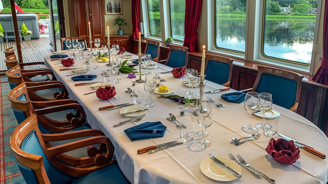 Dining table set for service with red, white & blue linens aboard Spirit of Scotland barge.