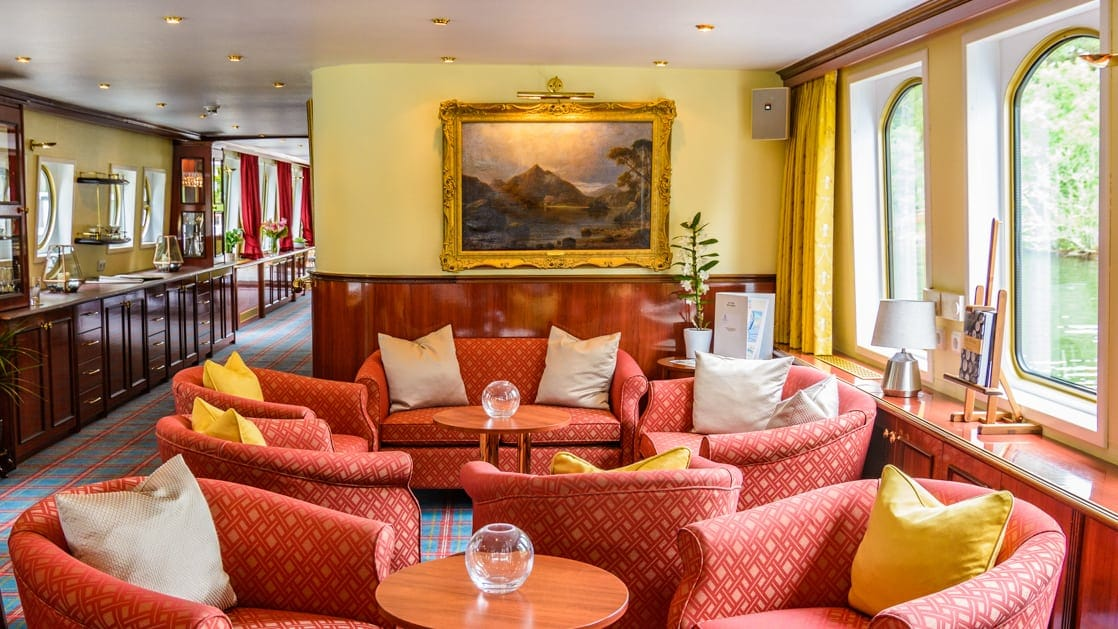 Saloon seating area with red fabric couch & chairs & large view windows aboard Spirit of Scotland riverboat.