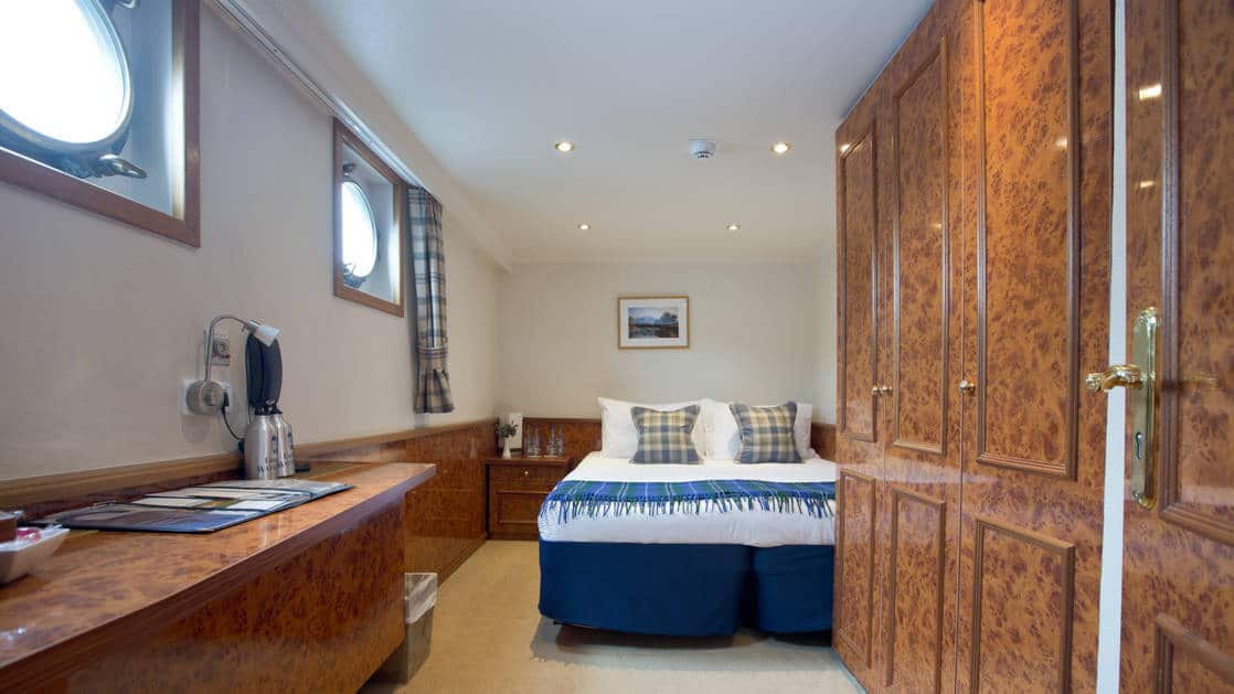 1 queen-sized bed with bedside table beside, 2 portholes, & walnut-wood large closet & desk aboard Spirit of Scotland hotel barge.