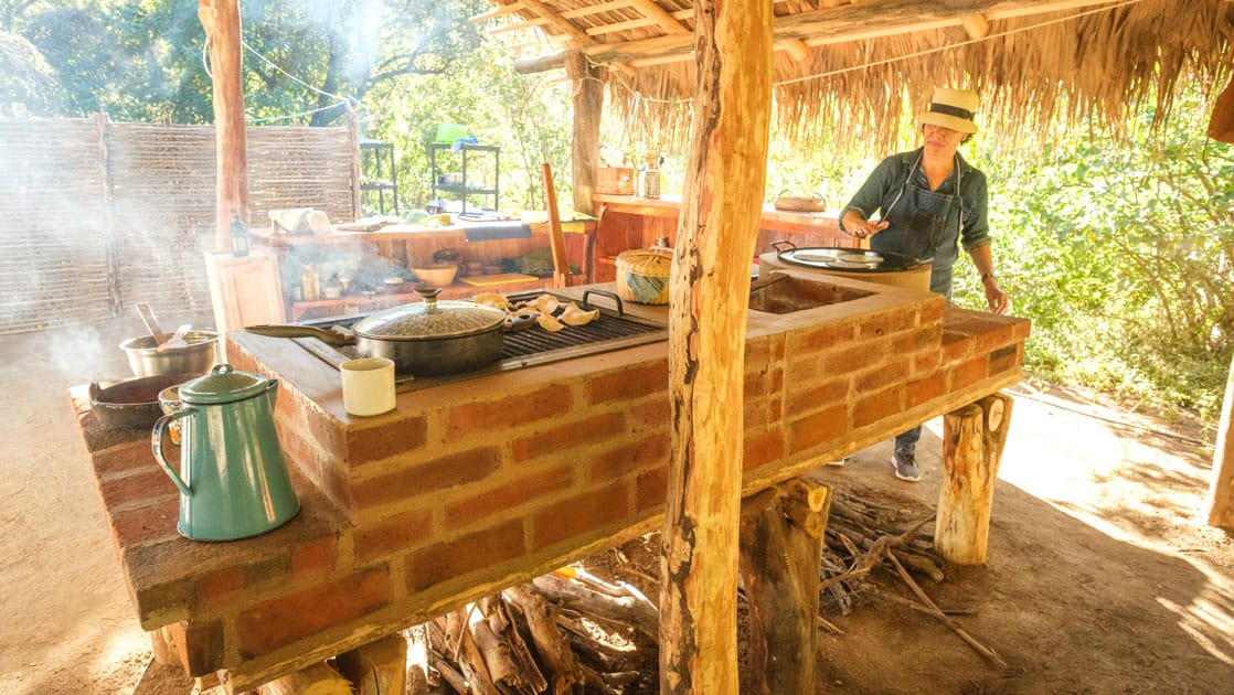 Woman stands over a brick stove making tortillas under a thatched roof on a sunny day at Camp Cecil de la Sierra.