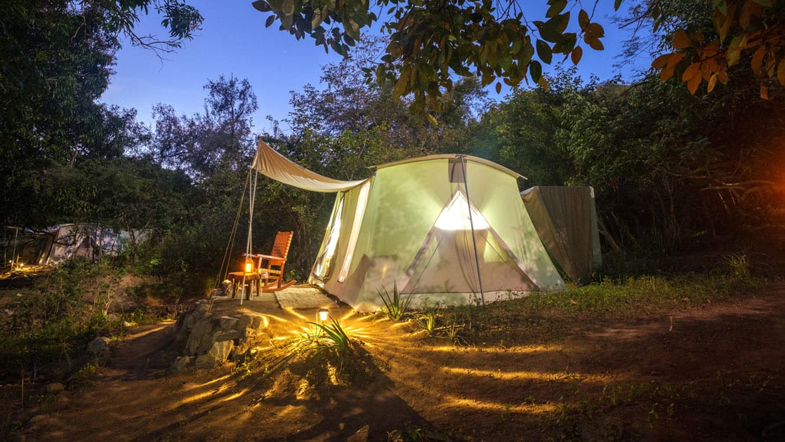 Exterior of Baja glamping tent lit up by lanterns at night.