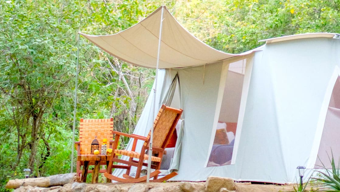 Canvas green & beige tent at Camp Cecil de la Sierra, with awning, 2 wooden rocking chairs & a table on a sunny day.