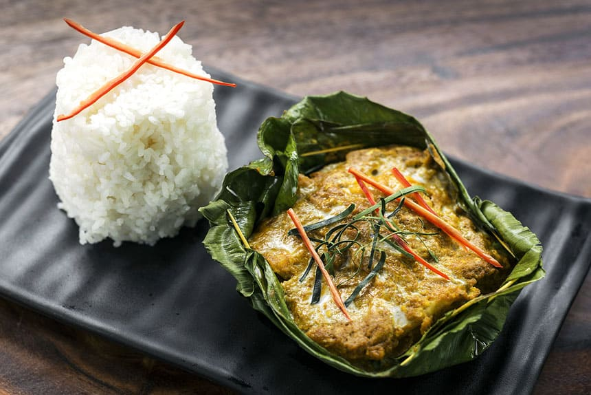 Chef David Thompson's Fish Amok Snakehead Curry presented in a green leaf with a cake of rice beside it on a black plate, offered during Aqua Mekong River Cruises.