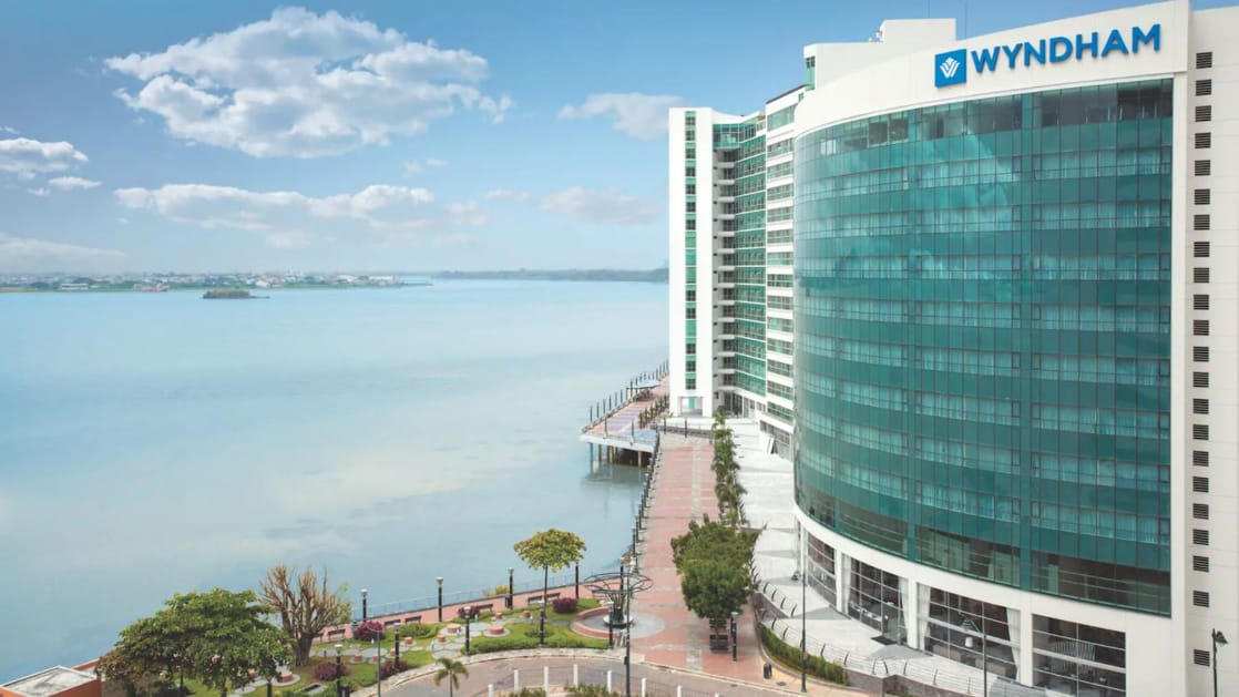 Exterior of Wyndham Guayaquil Hotel, multiple-story glass-encased building overlooking a large scenic river and a riverside walkway on a sunny day.