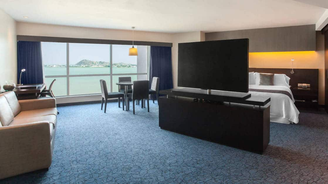 Junior Suite at Wyndham Guayaquil Hotel, with panoramic, floor-length windows, dresser & flat-screen TV separating bedroom from living area, table & chairs & double bed.