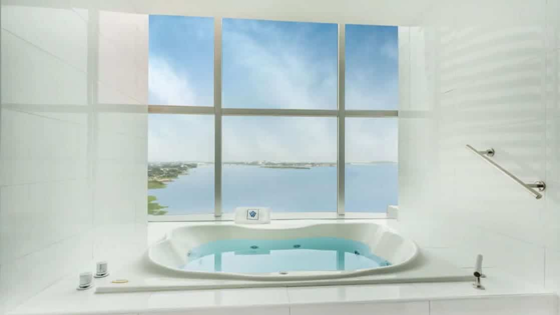 Presidential Suite white Jacuzzi with large windows looking out onto a sunny day & ocean at Wyndham Guayaquil Hotel.