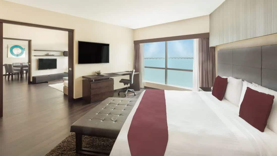 Presidential Suite bedroom at Wyndham Guayaquil Hotel with double bed, flat-screen TV, large windows & desk.