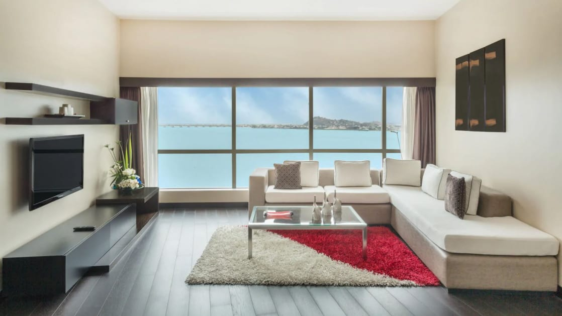 Presidential Suite living room at Wyndham Guayaquil Hotel with wraparound white couch, floor-length windows, flat-screen TV, coffee table, red-&-white rug & dark wooden flooring.