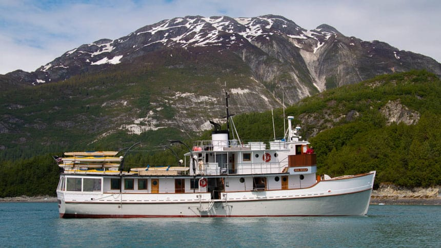 Sea Wolf historic Alaska small ship with 3 decks at anchor in front of green mountains topped with snow.