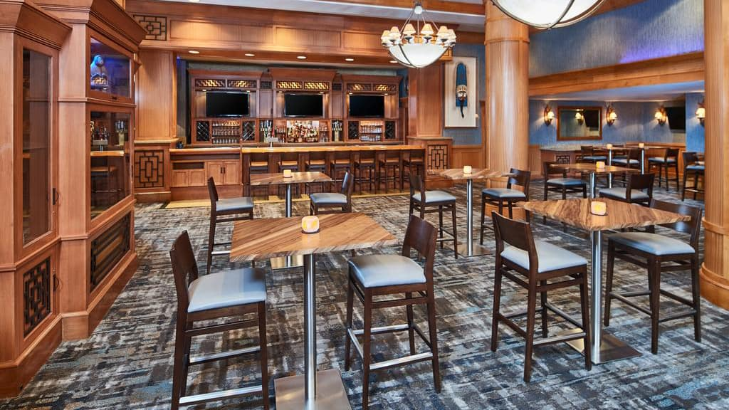 The bar and lounge of the Hilton Downtown Anchorage. Hit top tables anc chairs are set around the room with a wooden bar with flat screen tvs.