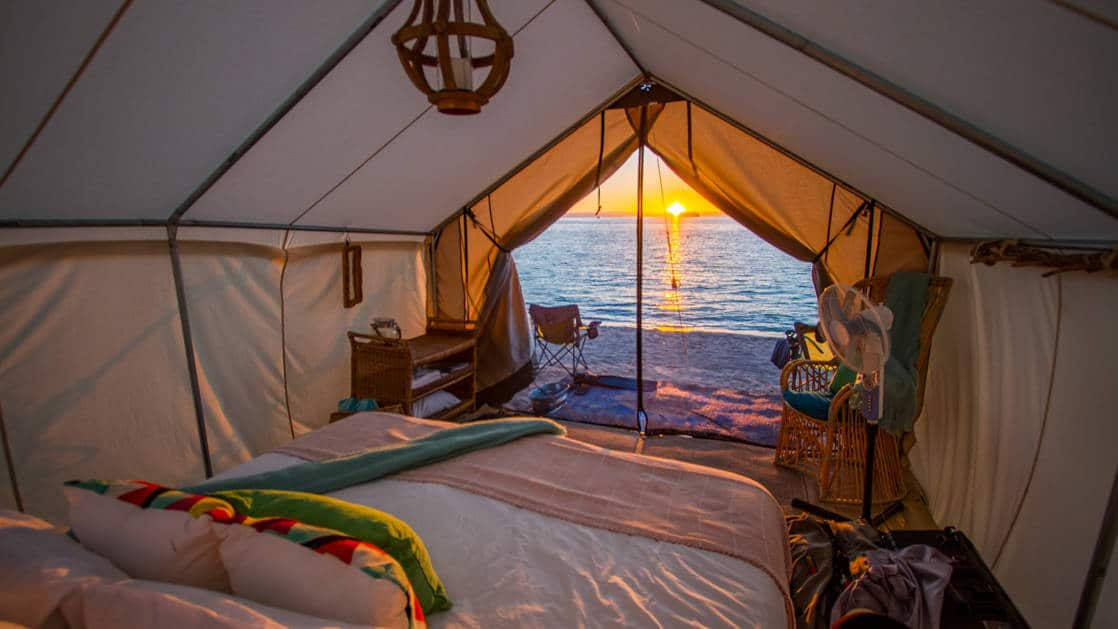 Luxury glamping tent at Camp Cecil on Isla Espritu Santo in Baja, looking out past double bed to sunset over the beach.