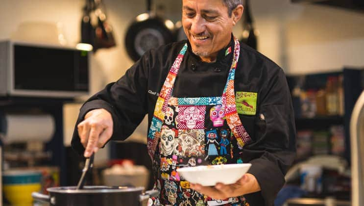 Male chef demonstrates how to cook a traditional Mexican dish in a kitchen while wearing a multicolored Day of the Dead apron during the Sea & Sierra: Glamping Baja California Sur land tour.
