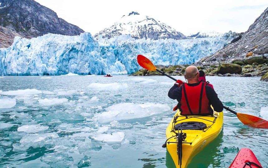 Man kayaking in alaska with a glacier in front of him.
