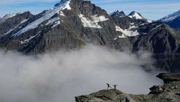 Two hikers' silhouettes in the fog mist high up in the New Zealand mountains with snow covered peaks.